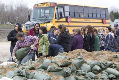 A long line of students are seen sandbagging around Saint Paul's Collegiate in Elie on Friday.