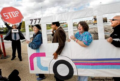 Members of the Winnipeg Rapid Transit Coalition protest near the Jubilee overpass Wednesday.