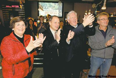 Alfie Risavy (right), owner of Alfie's bar and grill at 1042 Keewa­tin St., cheers for his Grey Cup favourites Sunday night with Win­nipeg North Liberal can­didate Kevin Lamoureux (third from right) and Liberal MPs Anita Neville (Winnipeg South Centre) and Bob Rae (Toronto­ Centre).
