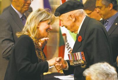 Annie Anne, vice-president of Lower Normandy, congratulates D-Day veteran Norman Donogh, who received a medallion for his service.