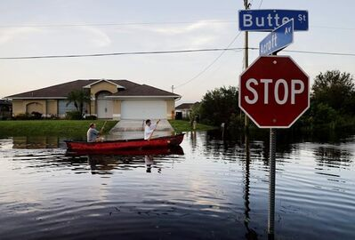 Pierre Ghantos, left, and his son Nathan paddle though their flooded neighborhood in the aftermath of Hurricane Irma in Fort Myers, Fla., Tuesday, Sept. 12, 2017. (AP Photo/David Goldman)