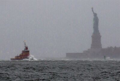 FILE - In a Monday, Oct. 29, 2012 file photo, waves crash over the bow of a tug boat as it passes near the Statue of Liberty in New York as rough water as the result of Hurricane Sandy churns the waters of New York Harbor. The Statue of Liberty survived Superstorm Sandy intact. But the storm flooded Liberty Island's power and heating systems and damaged its buildings. Superintendent David Luchsinger, who led reporters on a tour of Liberty Island on Friday, Nov. 30, 2012, says the National Park Service still does not know when the statue will reopen to the public or how much the island repairs will cost.� (AP Photo/Craig Ruttle, File)