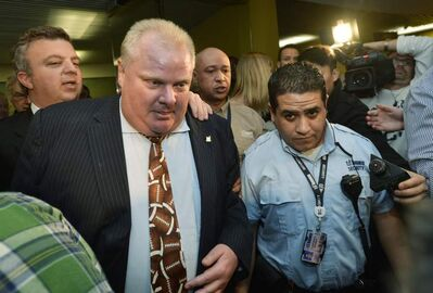 Toronto Mayor Rob Ford (left) goes to attend a toy-charity event at Toronto's city hall Monday shortly after a judge ordered him out of office for violating a conflict-of-interest law.