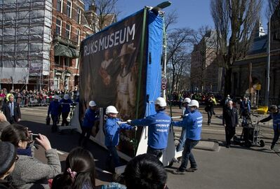Workers push a crate containing Dutch master Rembrandt's famous The Night Watch painting to its new location in the renovated Rijksmuseum, rear, in Amsterdam, Wednesday March 27, 2013. The museum will be opened officially on April 13, 2013, the crate was adorned with a reproduction of the painting. (AP Photo/Peter Dejong)