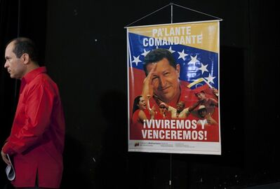"A poster of Venezuela's President Hugo Chavez that reads ""Move forward commander, we will live and overcome"" hangs as Venezuela's ambassador to Cuba Edgardo Antonio Ramirez stands by after a press conference by Cuban artists and intellectuals to show support for Chavez in Havana, Cuba, Monday, Jan. 7, 2013. Chavez hasn't spoken or appeared publicly since his Dec. 11 operation in Cuba, his fourth surgery for an undisclosed type of pelvic cancer. Speculation about the leader's condition has grown since the operation. (AP Photo/Ramon Espinosa)"