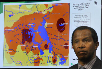 Manitoba Flood forecaster Phillip Mutulu framed by the new flood forecasting map at Tuesday's Provincial flood update.