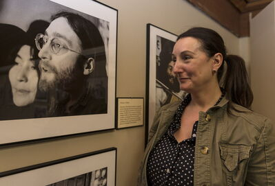 Curator Tracey Turner examines one of the many photos on display. It is the only staging of the Give Peace a Chance exhibit in Canada this year.