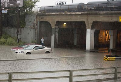 The overpass at Higgins Avenue and Main Street floods on Thursday afternoon after heavy rain.
