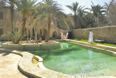People by a freshwater pool at the Ghaliet Ecolodge and Spa in the Egyptian oasis of Siwa. The palm tree-lined area is known for its quiet charm, ancient ruins, abundant natural springs, a vast salt lake and rolling sand dunes  in the surrounding desert.