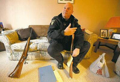 Photos by TREVOR HAGAN / WINNIPEG FREE PRESS  Const. Alan Akre collects hunting knives, ammo and a pair of rifles from a Winnipeg residence Thursday