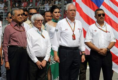 Malaysian Prime Minister Najib Razak, second right, stands with F1 boss Bernie Ecclestone, second left, former Prime Minister Mahathir Mohamad and Sepang International Circuit chairman Mokhzani Mahathir for a minutes silence for the missing passengers and crew on the ill-fated Malaysia Airlines flight MH370 prior to the start of the Malaysian Formula One Grand Prix at Sepang International Circuit in Sepang, Malaysia, Sunday, March 30, 2014. (AP Photo)
