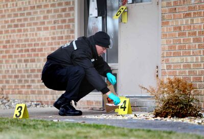 Winnipeg police forensic officer picks up a knife as he and other team members investigate Saturday.