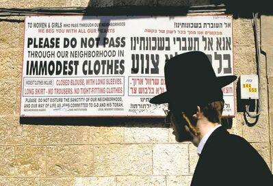 An ultra-Orthodox Jew walks past a sign calling on women to dress modestly in a religious neighbourhood in Jerusalem. In Israel's ultra-Orthodox Jewish community, the rule of law takes a back seat to the rule of God.