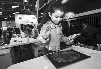 Samara Sepulveda, 5, makes a picture of the Earth at the Children's Museum's Mini Monday program during Earth Day.