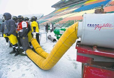 Freezing Hamilton players huddle to stay warm near sideline heaters during Wednesday's practice at Mosaic Stadium.