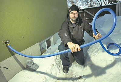 PHIL HOSSACK / WINNIPEG FREE PRESS FILES Ryan Black holds a hose that carries water to his home from a neighbour's.