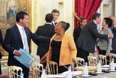 French Interior Minister Manuel Valls, left, greets French Justice Minister Christiane Taubira prior to a government seminar at the Elysee Palace in Paris, Monday Aug. 19, 2013. (AP Photo/Remy de la Mauviniere/Pool)