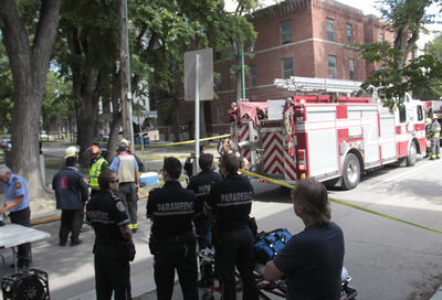 Emergency crews stand by on Assiniboine Avenue at Hargrave Street Tuesday afternoon.