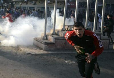 A demonstrator reacts to tear gas fired by security forces during clashes in Mahalla, Egypt.