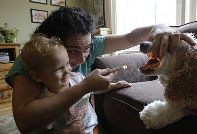 In this Thursday, Aug. 9, 2012 photo, Dr. Elisabetta Coletti, a Brooklyn-based veterinarian who makes house calls, examines her own pet Cocker Spaniel Milo as two year-old Leo, the son of Carrie Dirks Amodeo and partner Julie, watches during a house call to the family's home in New York. Coletti is part of a growing trend of family veterinarians who make house calls. (AP Photo/Kathy Willens)