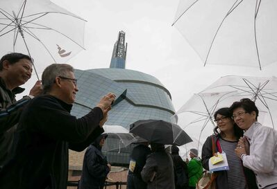 Frank Yong snaps a photo of his wife, Teresa, and her friend Jenny Lee, all from British Columbia, while they wait in the rain for their preview tour at the Canadian Museum for Human Rights on Saturday. The rain kept away some of the people with reserved tickets, allowing walk-ups to gain access to the guided tour of four of 11 galleries. The rest of the galleries open to the public Sept. 27.