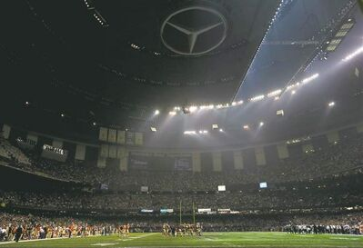 The night the lights went out in NOLA: players huddle at centrefield after a power outage left half the Superdome in darkness.