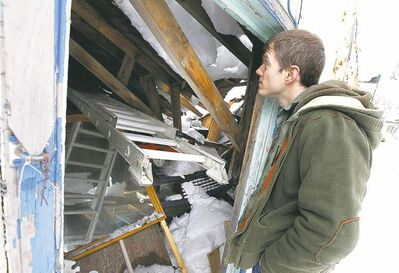 David Reid surveys the damage to his garage after its roof caved in early Sunday in Fort Rouge.