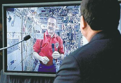 Astronaut Chris Hadfield unveils the new $5 bill while aboard the International Space Station as Finance Minister Jim Flaherty looks on at the Bank of Canada in Ottawa Tuesday.