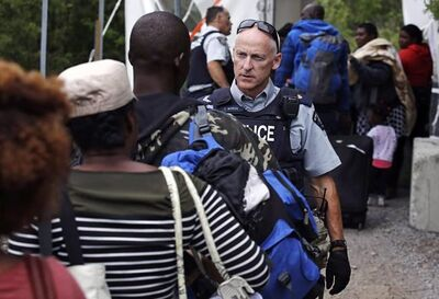 An RCMP officer standing in Saint-Bernard-de-Lacolle, Que., advises migrants that they are about to illegally cross from Champlain, N.Y., and will be arrested, Monday, Aug. 7, 2017. A spokesman for Public Safety Minister Ralph Goodale says an RCMP questionnaire that singled out Muslim asylum seekers has been deemed inappropriate and taken out of circulation. THE CANADIAN PRESS/AP/Charles Krupa