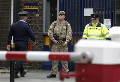 An armed soldier stands guard at the gate of the Royal Artillery Barracks near the scene of a terror attack in Woolwich, southeast London, Thursday, May 23, 2013. Police remained at the scene throughout the night after a brutal attack in a London street Wednesday, which left one member of the armed forces dead and two injured, and the two attackers were also hospitalised. The British government Cabinet's emergency committee immediately called a meeting and Prime Minister David Cameron's office said security was stepped up at barracks across London. (AP Photo/Sang Tan)