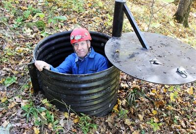 In this Oct. 10, 2013, photo, John Ackerman poses in a shaft entrance to his Temple of Doom, one of the 37 caves on his property near Spring Valley, Minn. Ackerman estimates he's spent $4 million on cave exploration and acquiring underground rights, but he doesn't charge admission to the nature groups, scientists and cavers who visit. It's a hobby made possible by his successful furniture restoration business, he said. (AP Photo/Jeff Baenen)