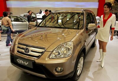 FILE - In this April 21, 2005 file photo, a model poses by a Honda's CR-V at Auto Shanghai 2005 exhibition in Shanghai, China. Honda, Mazda and Nissan are recalling millions of vehicles globally for defective airbags manufactured by supplier Takata Corp. that could possibly explode. No accidents have been reported related to recalls Monday, June 23, 2014. Honda Motor Co. recalled 2.03 million vehicles for the airbag problem, including 1.02 million in North America and nearly 669,000 in Japan. The models recalled at Honda include the Fit, Element and CR-V, manufactured between 2000 and 2005. (AP Photo/Eugene Hoshiko, File)