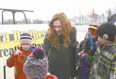 Clara Hughes lets children see her Olympic medals at ceremony in Elmwood Saturday.