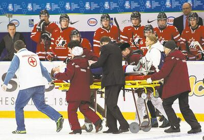 Slovakia forward Patrik Luza, leaves the ice on a stretcher after being crunched along the boards by Canada's Anthony Camara during second period action at the world junior tournament in Ufa, Russia Friday.
