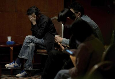 Relatives of the Chinese passengers aboard the missing Malaysia Airlines Flight MH370 wait for the latest news of the plane at a hotel ballroom in Beijing, China, Thursday. Australian rescue officials say a search in the southern Indian Ocean for possible objects from the missing Malaysia Airlines plane has ended for the day but will resume in the morning.