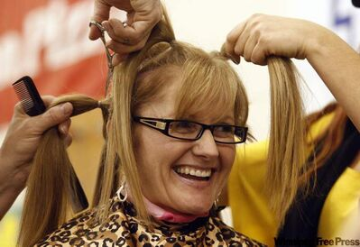 Sandra Bellingham honours the memory of her husband WPS Staff Sgt. Wayne Bellingham who died of cancer 11 years ago by getting her head shaved this morning at Robert H. Smith School. Over $7,000 was raised for CancerCare Manitoba at the community breakfast.