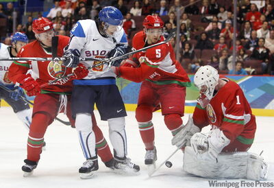 Belarus' goalie Vitali Koval (1) blocks a shot as teammates Vladimir Denisov (7) and Nikolai Stasenko (5) keep Finland's Teemu Selanne (8) away from the rebound during the second period of a preliminary round men's ice hockey game at the Vancouver 2010 Olympics in Vancouver, British Columbia, Wednesday.