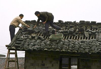 In this photo released by China's Xinhua News Agency, villagers repair the roof of a house at Shuangxi Village of Shuangxi Township in Jing'an County, east China's Jiangxi Province, Saturday, March 23, 2013. Hailstorms that hit southern China this week have killed a dozen of people, injured hundreds more and caused millions of dollars in damage. (AP Photo/Xinhua, Xu Zhongting) NO SALES