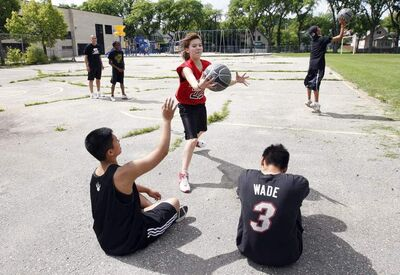 Inner-city kids play hoops on a rundown court behind William Whyte School.