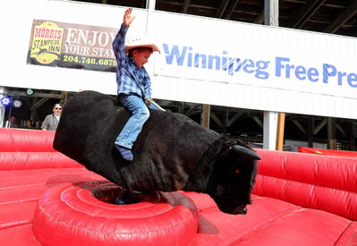 Zac McKenzie, 4, rides a mechanical bull at the Morris Stampede Saturday. The annual rodeo continues Sunday.