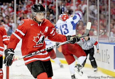 Team Canada's Brayden Schenn skates away as Team Russia's Maxim Kitsyn celebrates his third-period goal in the gold-medal final in Buffalo, N.Y., Wednesday.