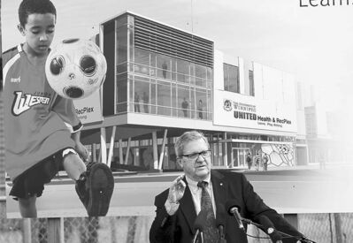 University of Winnipeg president Lloyd Axworthy speaks in front of an artist's rendering of the United Health & RecPlex.