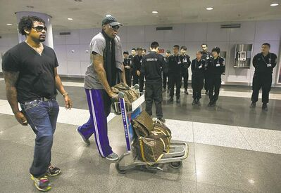 Former NBA star Dennis Rodman, (center) pushes his luggage pass through a group of Chinese security officers as he makes his way to the check- in counter at the departure hall of Beijing Capital International Airport Tuesday.