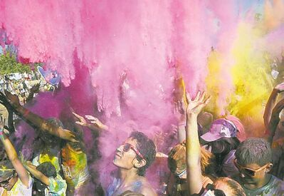 Participants take in the community color bombing after the finish line during the Color Me Rad 5K event held at Fresno, Calif., last year.