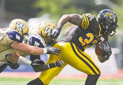 Mark Blinch / REUTERSTiger-Cats running back C.J. Gable busts free of Blue Bombers Demond Washington (centre) and Rene Stephen on Saturday afternoon in Guelph.