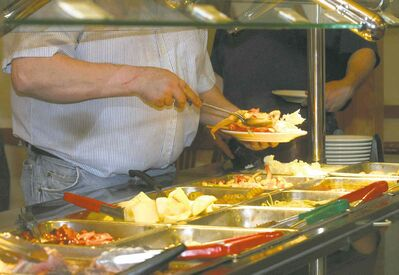 A hungry diner loads his plate with some of the dizzying array of food from buffet table.