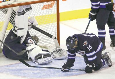 Jets goaltender Ondrej Pavelec sprawls in the net after the puck took a strange bounce off Matt Halischuk (15) and crossed the line. Ottawa's Milan Michalek got credit for the goal.