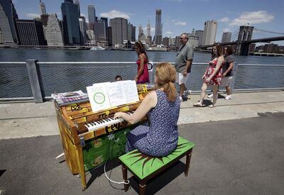 FILE - In this file photo of June 21, 2010, Carolyn Enger, of Englewood, N.J., plays a piano in Brooklyn Bridge Park, in the Brooklyn borough of New York. The piano was one of 60 that were part of the first year of Sing for Hope's Pianos, a grassroots group of over 1,000 artists who volunteer to make art accessible to everyone. (AP Photo/Richard Drew, File)