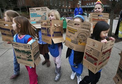 FILE - Dressed in boxes emptied from earlier cookie sales, Girl Scouts from Troop 20337 in Eugene, fan out on the University of Oregon campus near the Erb Memorial Union in Eugene, Ore., Monday, Feb. 18, 2013 in search of customers for their cookies. Just a year after its 2012 centennial celebrations, the Girl Scouts of the USA's interconnected problems include declining membership and revenues, a dearth of volunteers, rifts between leadership and grass-roots members, a pension plan with a $347 million deficit, and an uproar over efforts by many local councils to sell venerable summer camps. (AP Photo/The Register-Guard, Chris Pietsch)