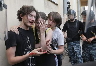 Riot police (OMON) guard gay rights activists who have been beaten by anti-gay protesters during an authorized gay rights rally in St.Petersburg, Russia, Saturday, June 29, 2013. Police detained several gay activists, who were outnumbered by the protesters. Dozens of gay activists had to be protected by police as they gathered for the parade, which proceeded with official approval despite recently passed legislation targeting gays.
